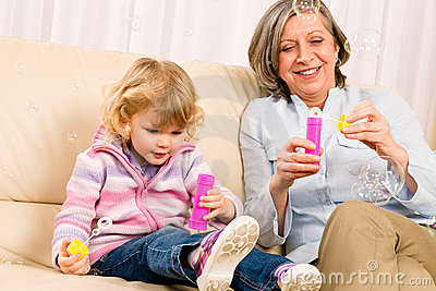 Little girl with grandmother play bubble blower