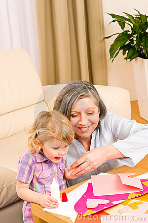 Little girl with grandmother play glue paper