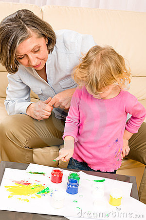 Little girl with grandmother play paint handprints