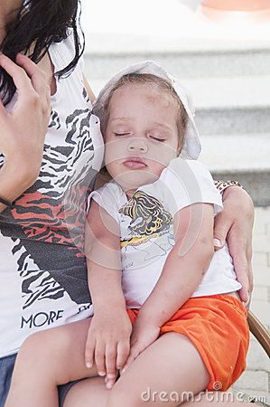 Little girl had fallen asleep on hands of his mother