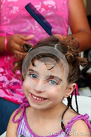 Little girl in hairdresser preparing braided hair