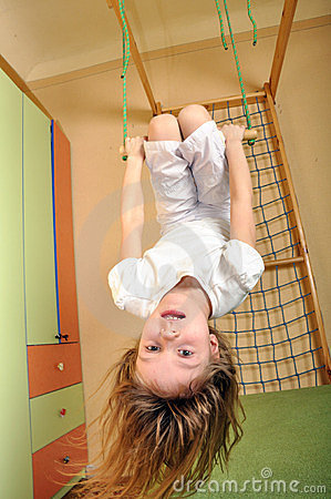Little girl hanging down at gym