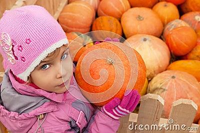 Little girl has got pumpkin from box