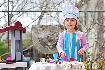 Little girl having fun playing cooking
