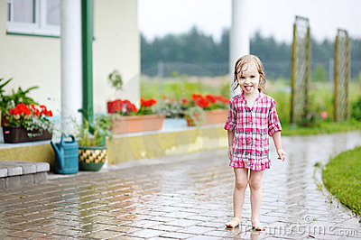 Little girl having fun under the rain