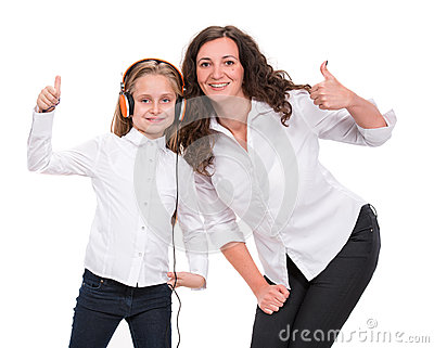Little girl in headphones listening to music and mother