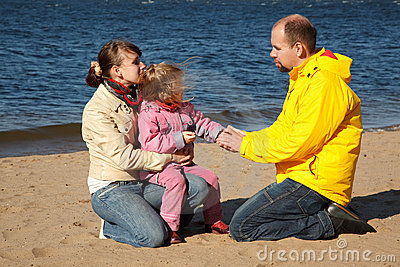 Little girl with her parents at beach