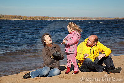 Little girl with her parents played on beach