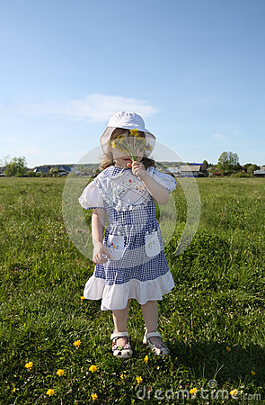 Little girl hides her face in yellow dandelions