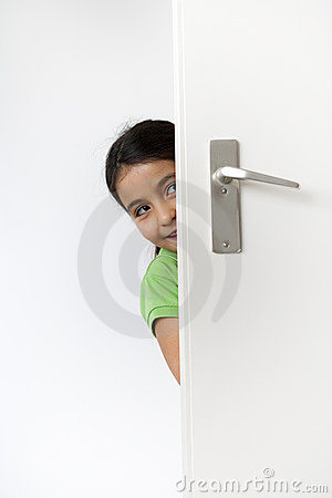 Little girl is hiding behind the door