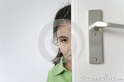 Little girl is hiding behind the door