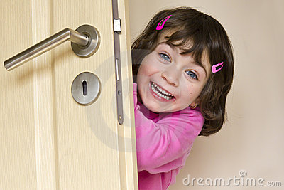 Little girl is hiding behind a door