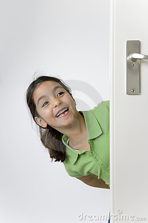 Little girl is hiding behind the door for fun
