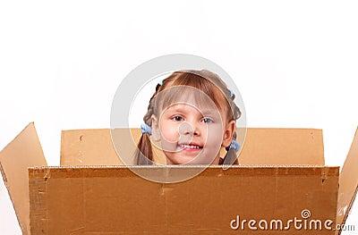 Little girl hiding in cardboard box