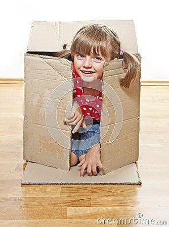 Little girl hiding inside paper box