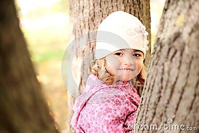 Little girl hiding in the trees in autmn park