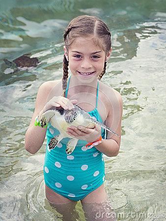 Little Girl holding a baby sea turtle
