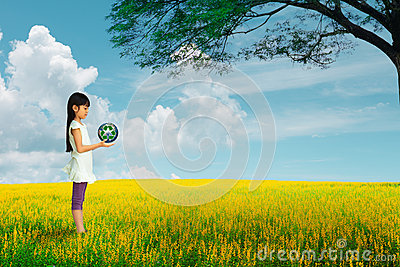 Little girl holding earth with recycle symbol at flower field