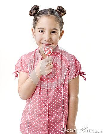 Little girl holding an hart shaped lollipop