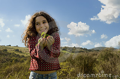 Little girl holding plant