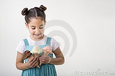 Little girl holding three ice cream cones