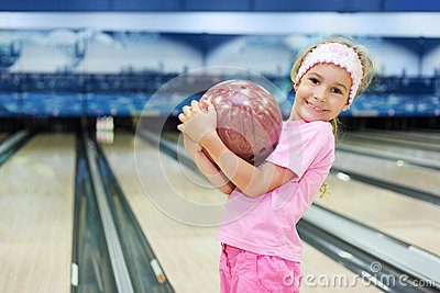 Little girl holds ball in bowling club