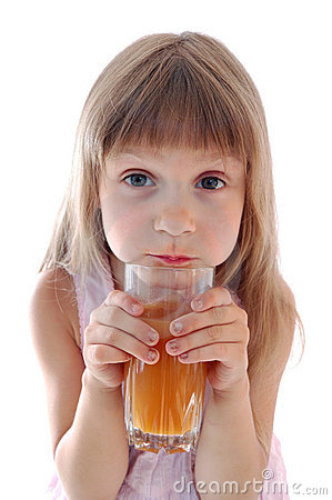 Little girl holds glass of  juice.