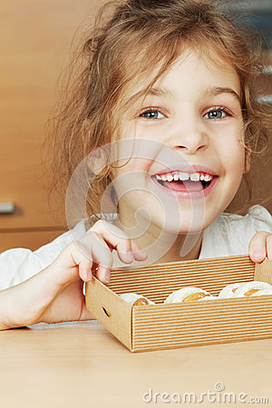 Little girl holds open box of corrugated cardboard with cookies