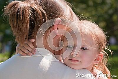 Little girl hugging her mother s neck