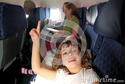Little girl inside aircraft rising up finger