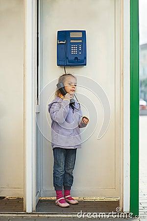 Little girl in jacket on landline