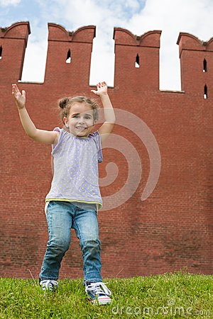 Little girl in jeans have fun and raised hands up