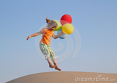 Little girl jumping with balloons
