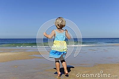 Little girl jumping on the beach