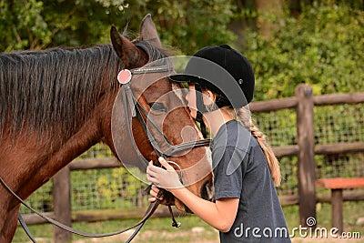 Little girl kissing her pony