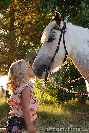 Little girl kissing pony.
