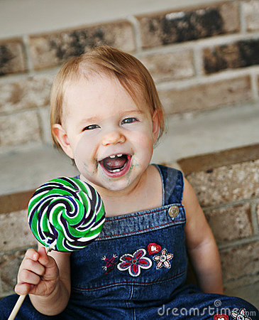 Little girl laughing holding a lollipop