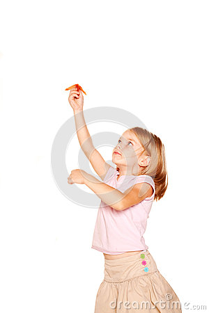 Little girl launching up paper plane