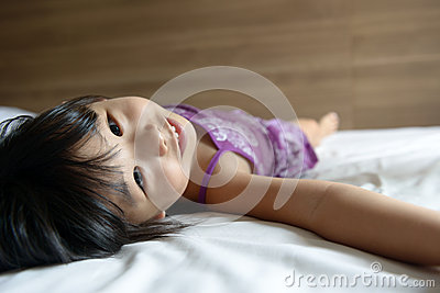 Little girl laying on bed