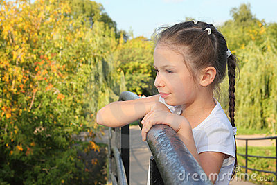 Little girl is lean elbow on bridge fence