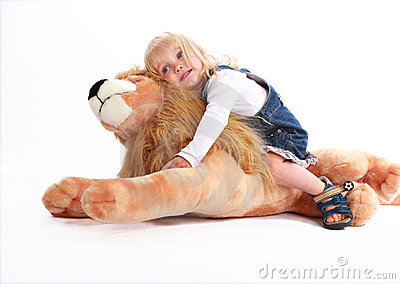 Little girl leaning on a toy lion Stock Photo