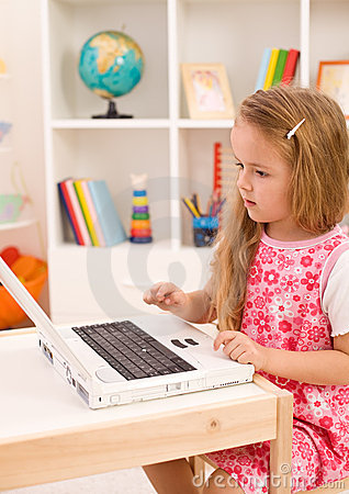 Little girl learning to handle a laptop computer