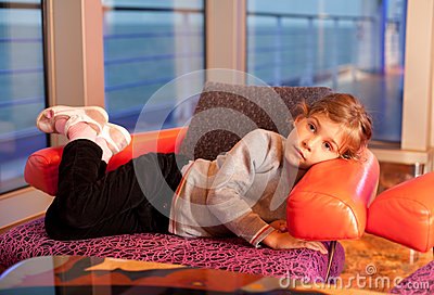 Little girl lie in chair in cabin in ship