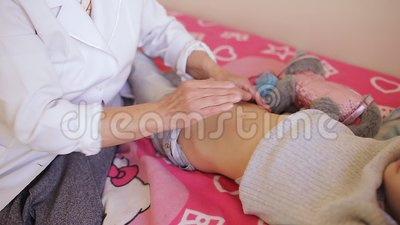 The Elderly Woman Masseur Doing Massage Of The Abdomen To The Little Girl In The Hospital. Stock Video - Video of pain, massaging: 128693577