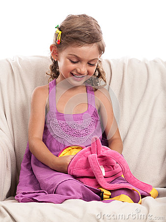 Little girl looking in backpack on sofa isolated