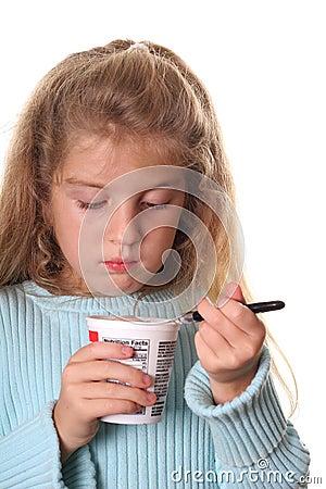 Little girl looking at her yogurt vertical