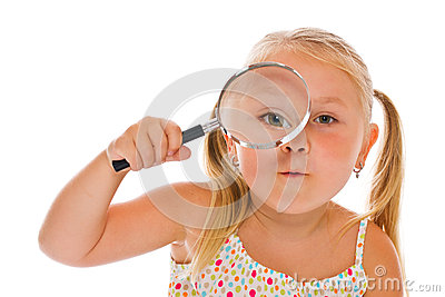 The little girl looking through a magnifying glass