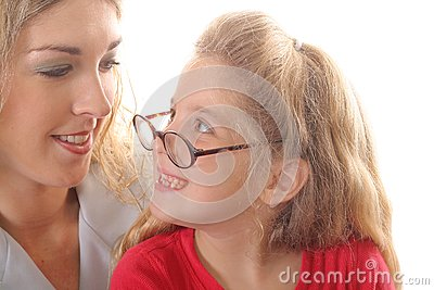 Little girl looking at mom with glasses smiling