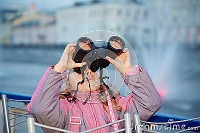 Little girl looks through binoculars at sunset