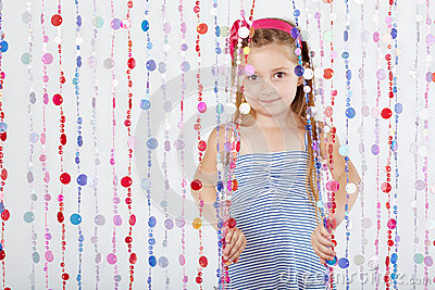 Little girl looks out from behind curtain